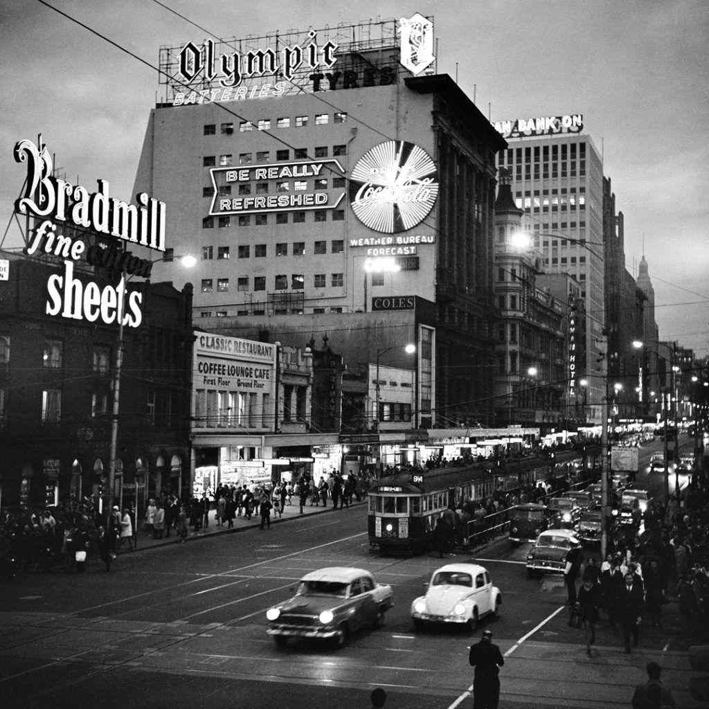 A black and white photo of a city street at night