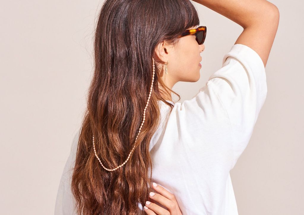 A woman with long hair wearing sunglasses with a gold chain attached to the arms that loops down her back