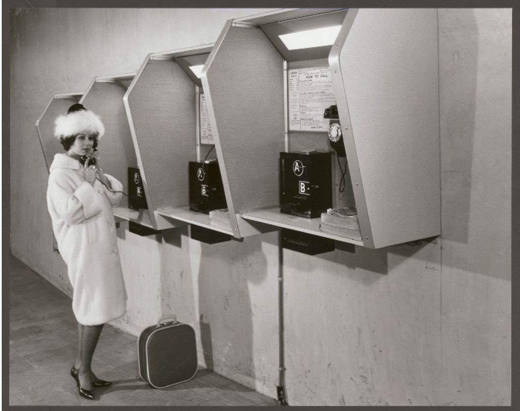 A black and white photo of a woman at a phone booth