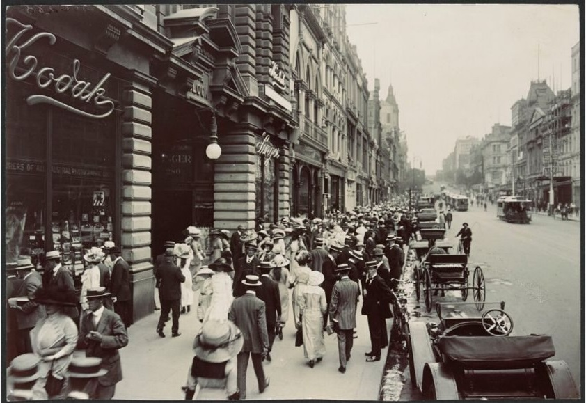 A black and white photo of a busy shopping street