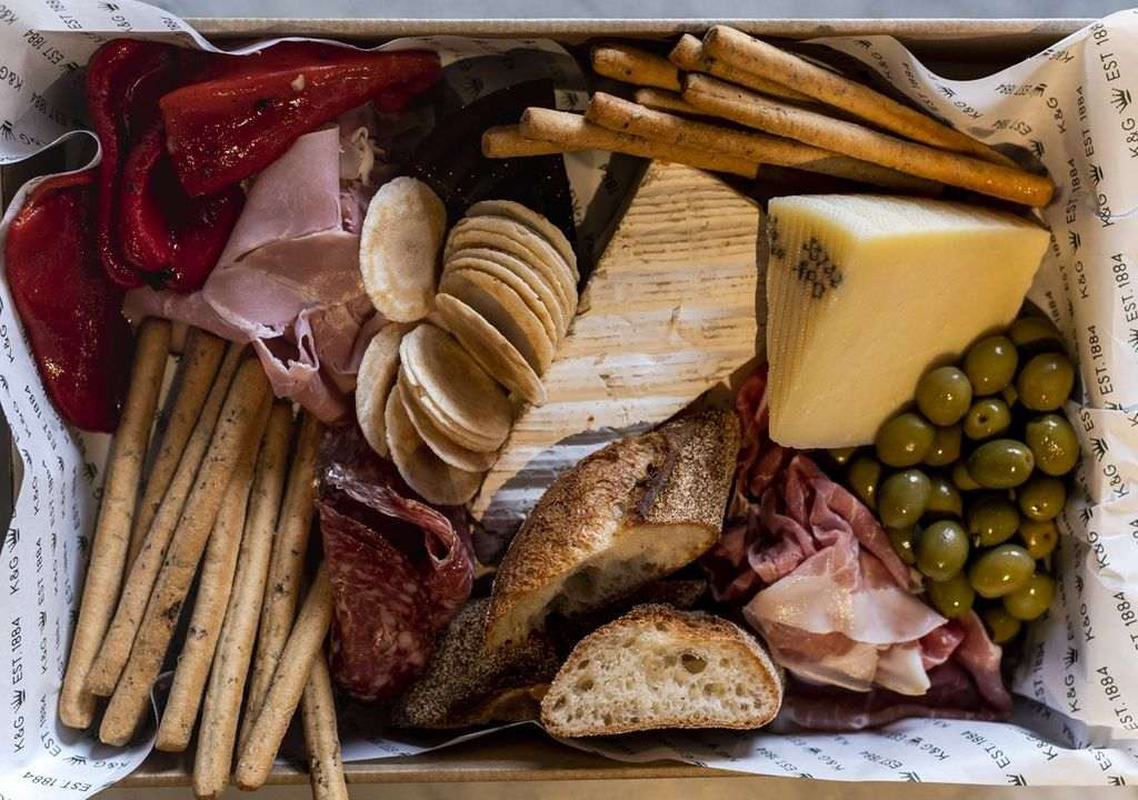 A box filled with deli meats and crackers