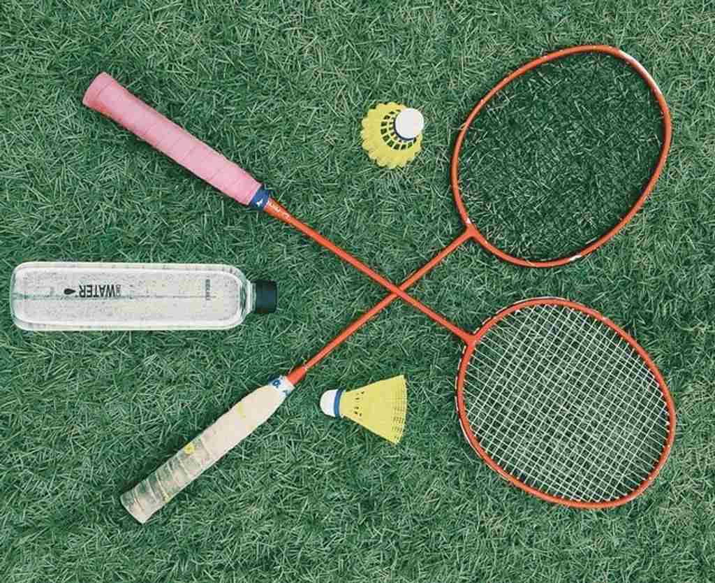 Two racquets with a shuttlecock on grass