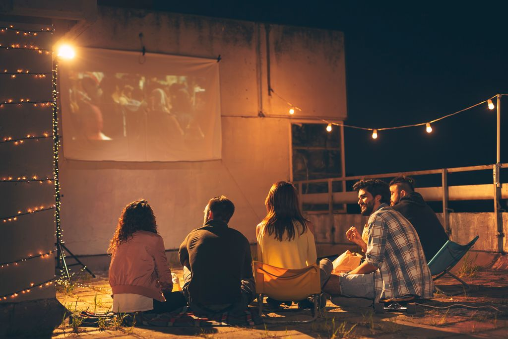 A group of young people on a rooftop watching a projector screen