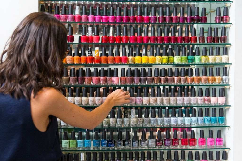 A woman looking at a shelf of nail polishes