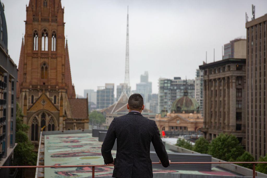 A man on a rooftop looking over the city