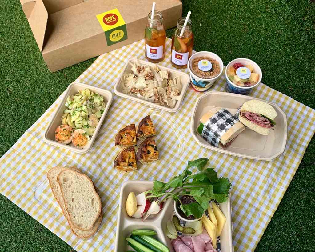 Sandwiches and drinks on a picnic mat