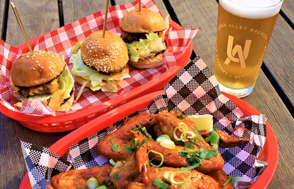 Burgers and wings on a table with a beer