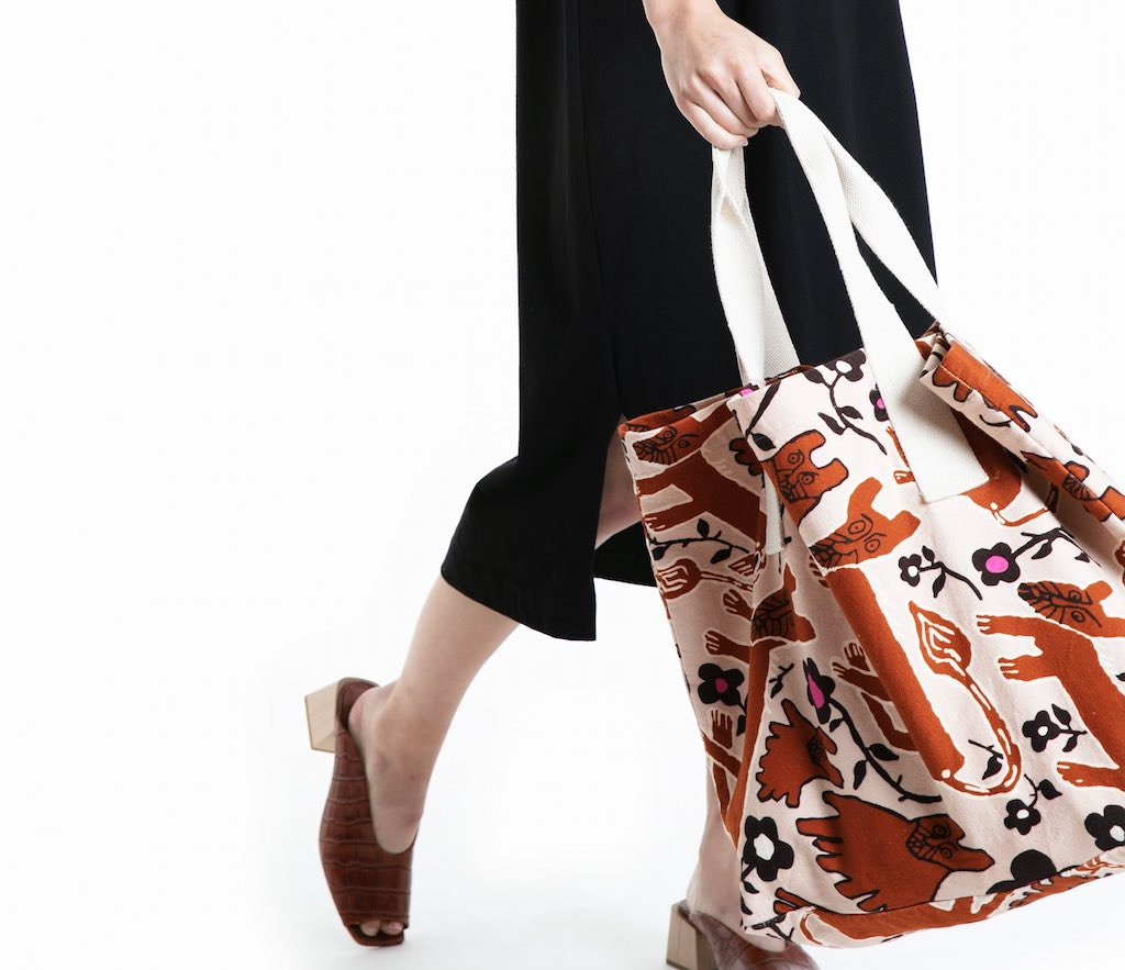 Person holding large tote bag from Obus