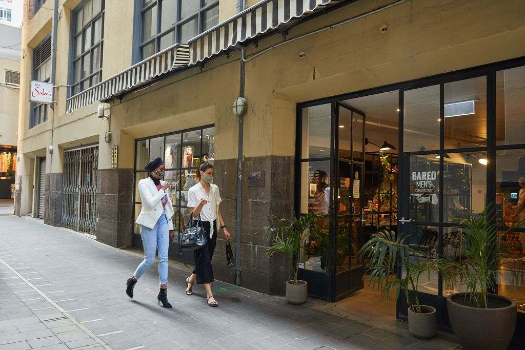 Two women walking off the street into a shoe shop